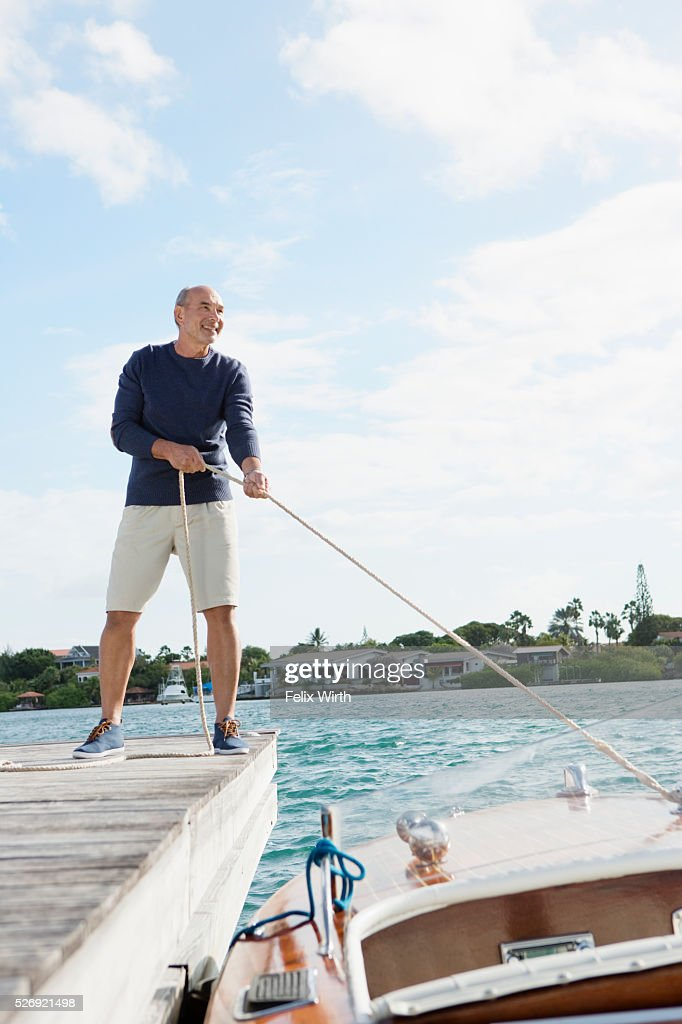 Senior man standing on jetty with moored motorboat : Stock Photo