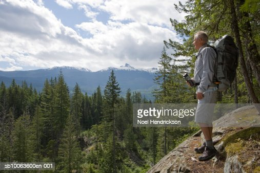 Senior man standing on mountain top, looking at view, carrying backpack : Foto de stock