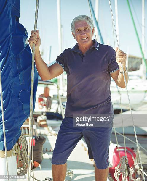 Senior man standing on yacht, holding onto cables, smiling, portrait