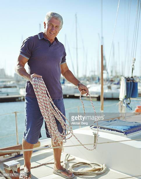 Senior man standing on yacht, looping length of rope, portrait