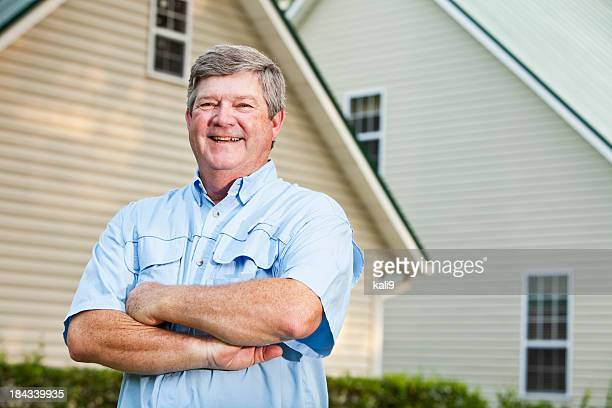 Senior man standing outside home
