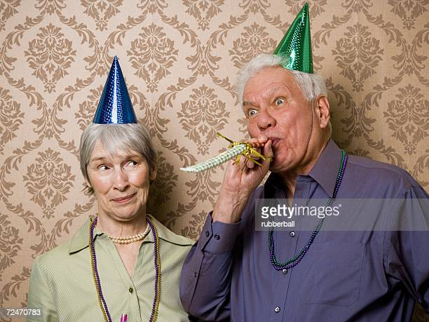 A senior man standing with a senior woman and blowing a party favor