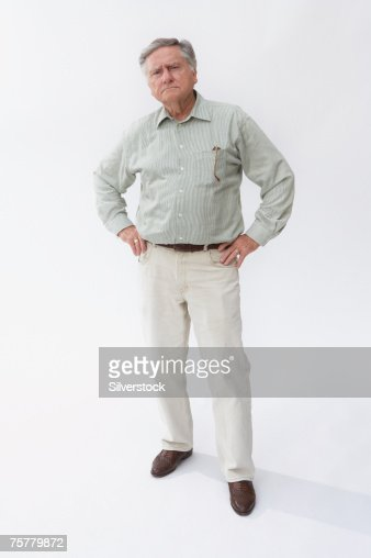 Senior man standing with hands on hips against white background, portrait : Stock Photo