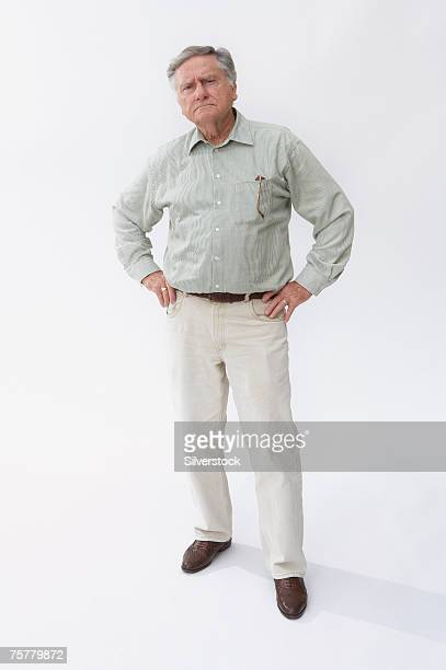 Senior man standing with hands on hips against white background, portrait