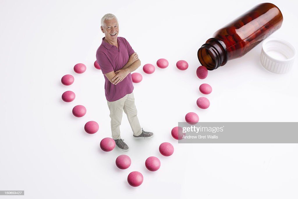 Senior man stands amongst heart-shaped pills : Stock Photo