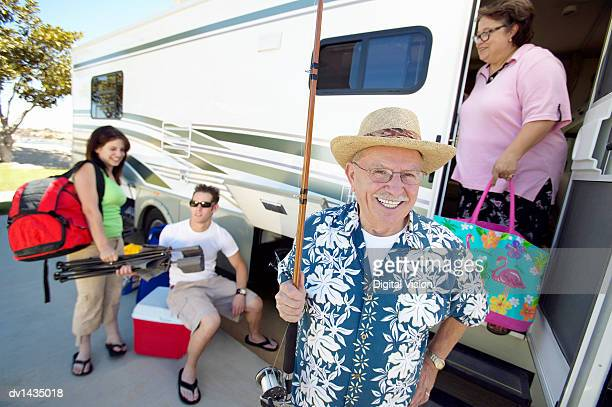Senior Man Stands in Front of a Motor Home, Holding a Fishing Rod, His Wife and Grandchildren Unloading Luggage