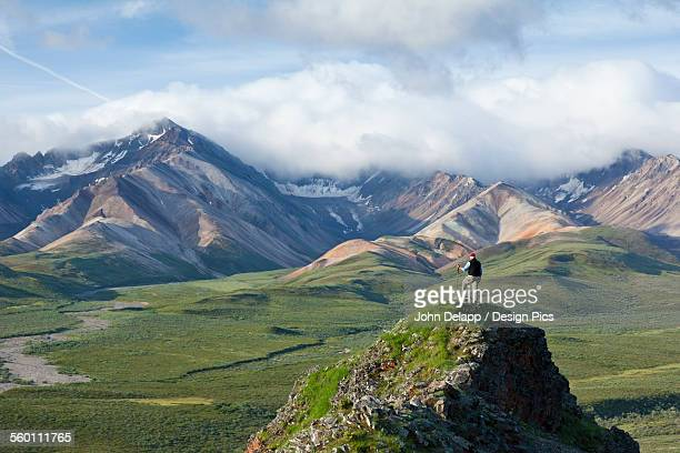 Senior Man Stands On A Rock Outcrop At Polychrome Pass With Alaska Range In The Background, Denali National Park & Preserve, Interior Alaska, Summer