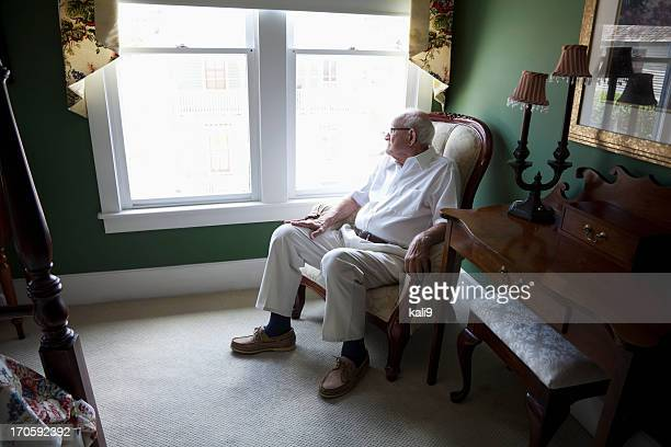 Senior man staring out a window