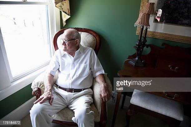 Älterer Mann schaut aus dem Fenster
