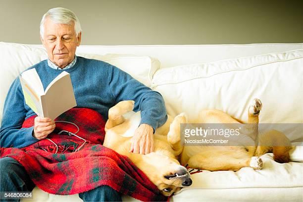 Senior man stroking his dog while reading a book