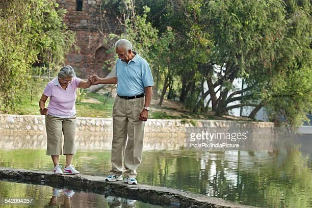 Senior man supporting woman while walking on narrow bridge at park