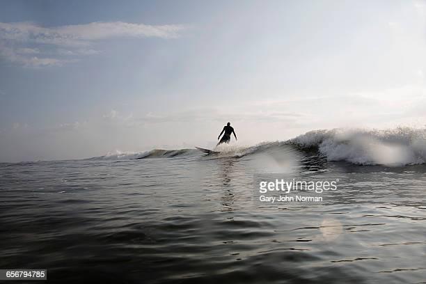Senior man surfing a wave, silhouette