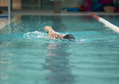 Senior man swimming in freestyle - Concept of sport and fun in swimming pool