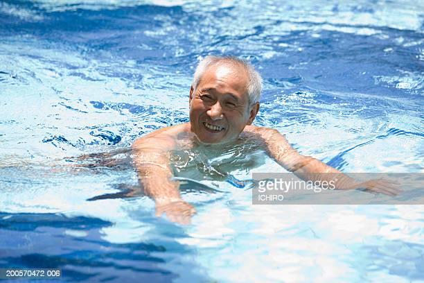 Senior man swimming in pool, smiling