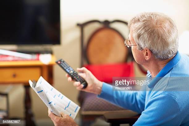 Senior man switching on TV