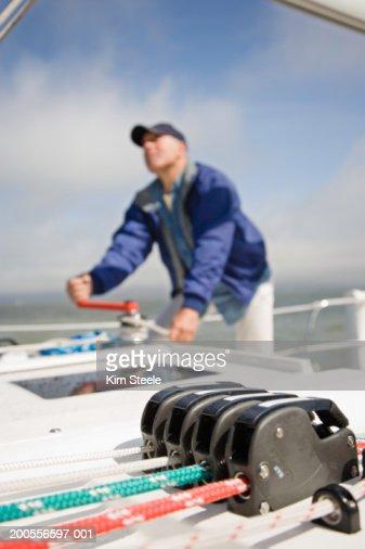 Senior man tacking yacht, focus on rope at foreground