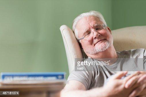 Senior man taking a nap in a chair