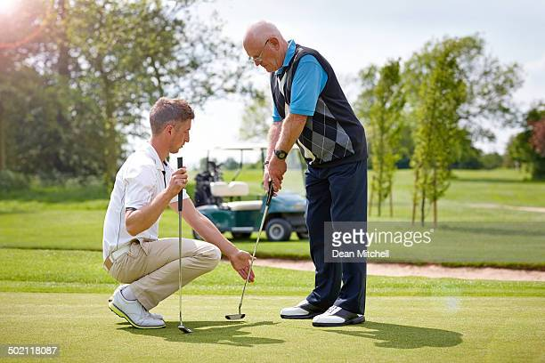 Senior man taking golf lessons from club pro