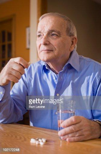 Senior man taking his medication : Stock Photo