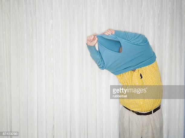Senior man taking off his sweater