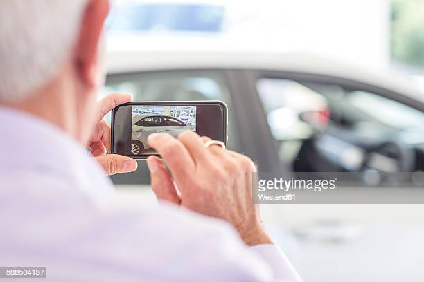 Senior man taking picture of a new car in showroom