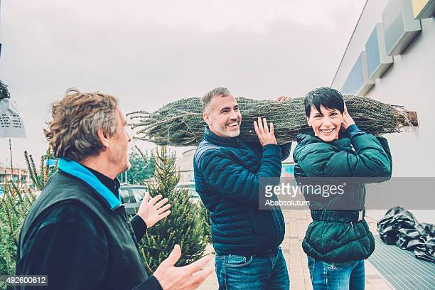 Senior Man Talking, Happy Couple Carrying Christmas Tree, Europe