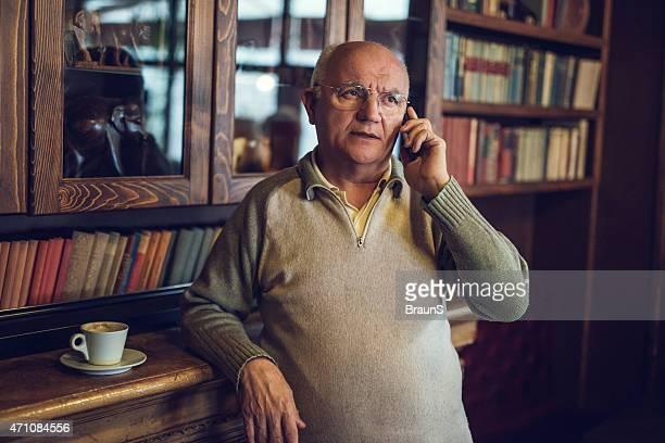 Senior man talking on mobile phone at home.