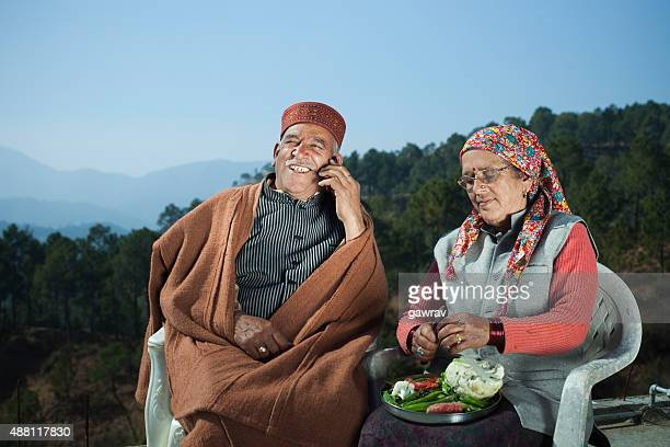 Senior man talking on phone and his wife cutting vegetables.