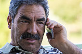 Senior man talking on phone with shocked expression. Shocked senior man listening phone and raising eyebrows. He is wearing casual clothes. Man sitting. Focus on shocked senior man. Horizontal composi