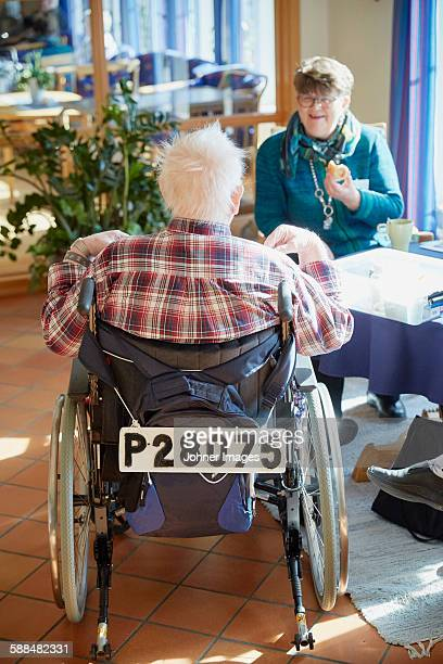 Senior man talking with nurse in care home