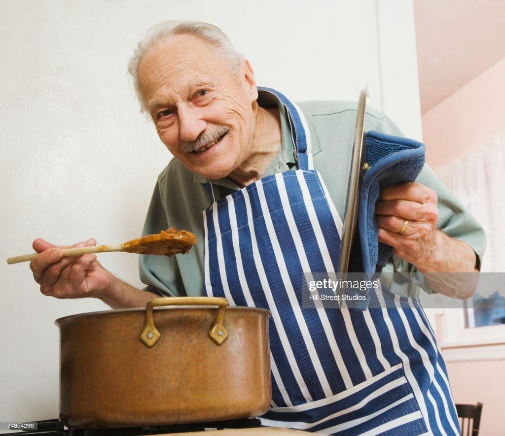 Senior man tasting food in kitchen : Stock Photo