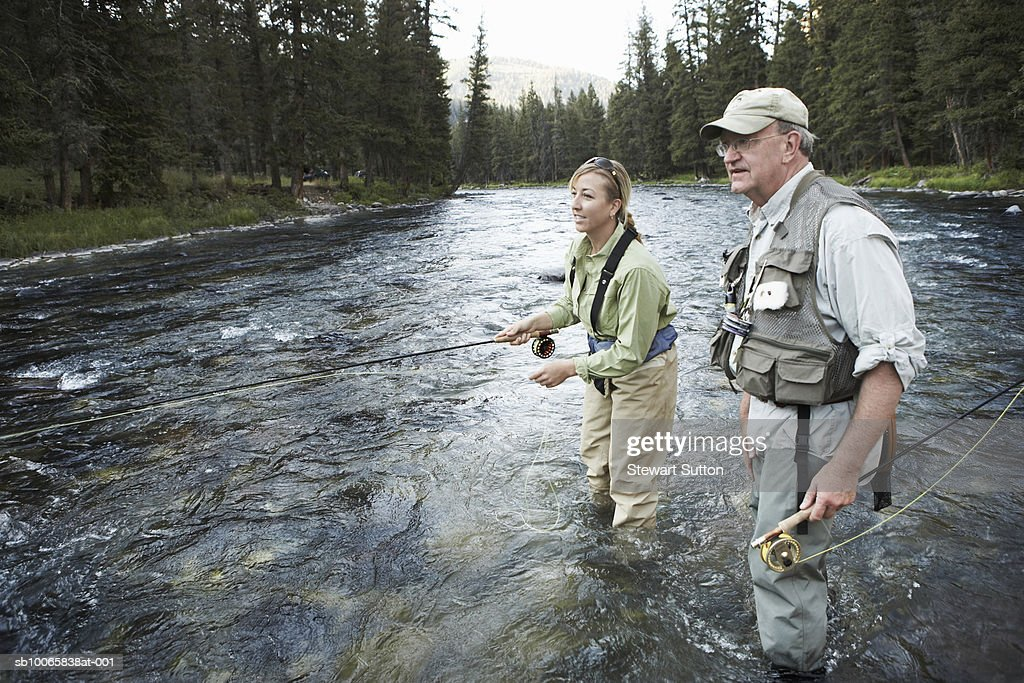 Senior man teaching woman fly-fishing : Stockfoto