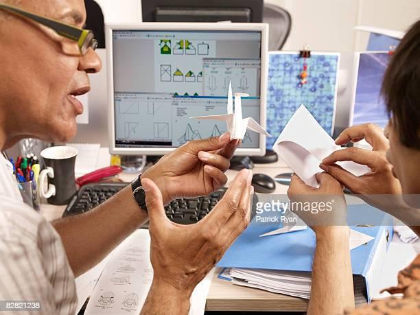 senior man teaching young man some origami