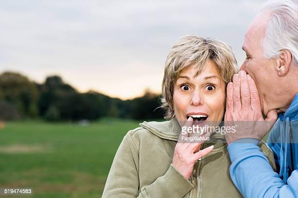 Senior man telling woman secret, outdoors, portrait