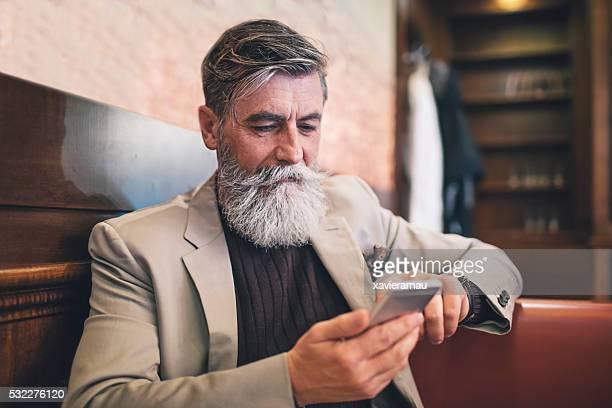 Alter Mann SMS auf Mobiltelefon