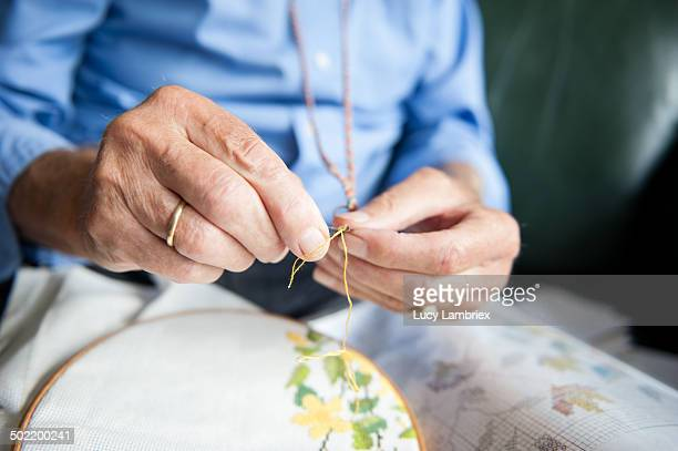 Senior man threading a needle for embroidery work