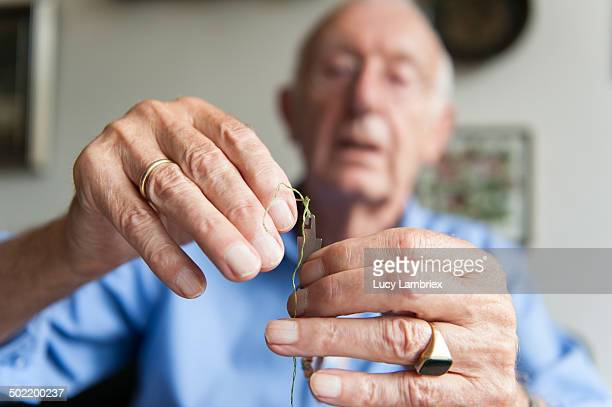 Senior man threading his embroidery needle
