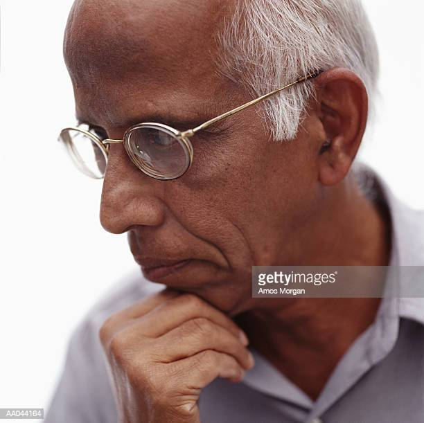 Senior man touching chin with hand, side view, close-up