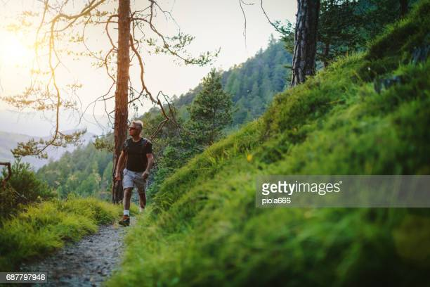 Senior man trail hiking in a mountain forest