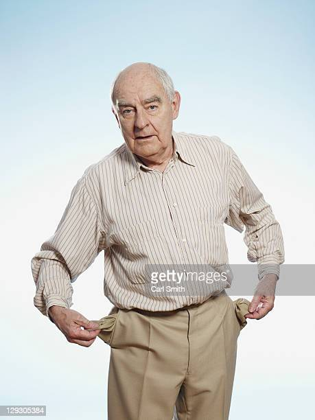Senior man turns his pockets inside out to symbolize having no money