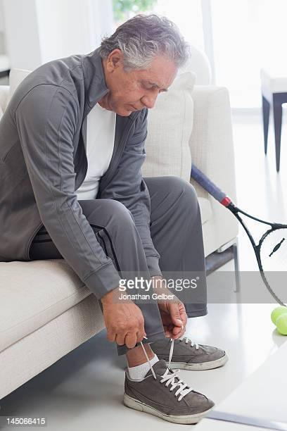 A senior man tying his shoelaces, preparing to play tennis