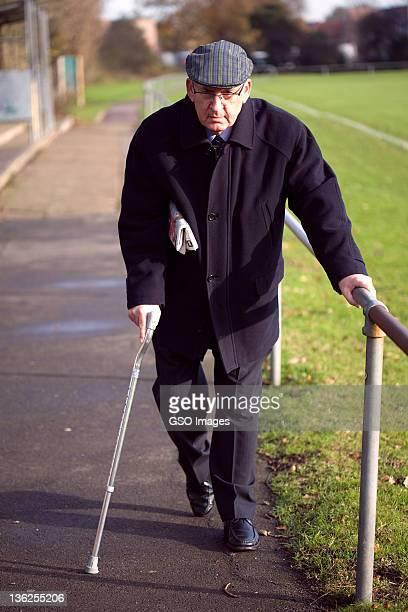 Senior man uses crutch whilst walking