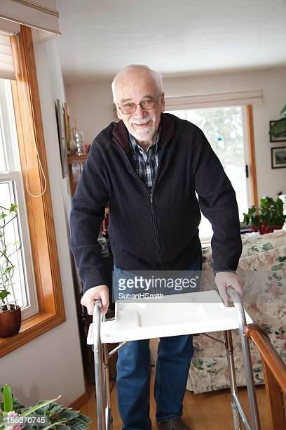 A senior man using a walker in a home