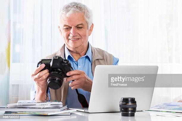 Senior hombre con cámara y su computadora portátil