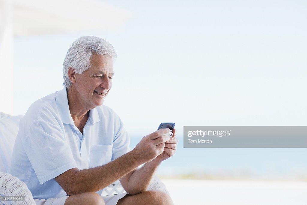 Senior man using cell phone on beach patio : Stock Photo