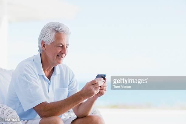 Senior man using cell phone on beach patio