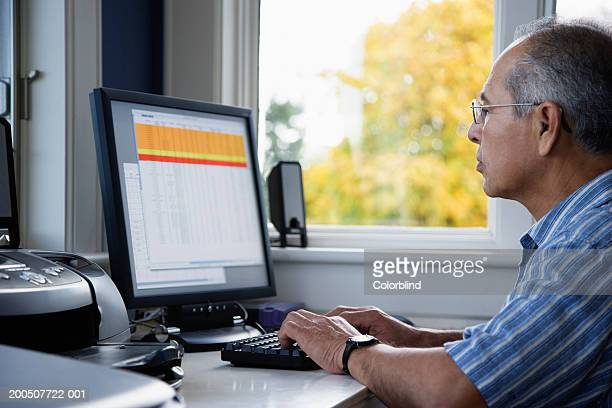 Senior man using computer at home, side view