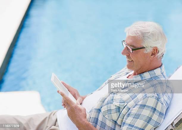 Senior man using digital tablet at poolside