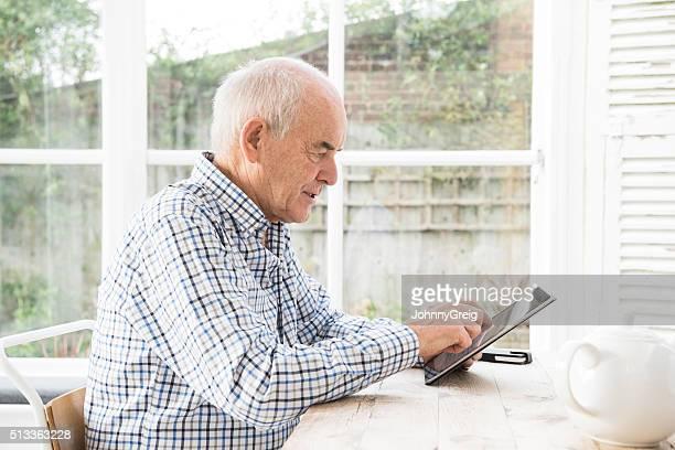 Homme Senior à l'aide de tablette numérique avec expression grave