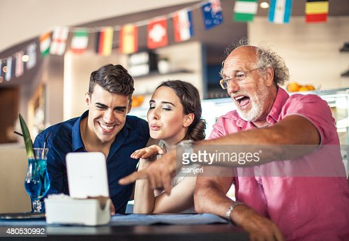 Senior man using digital tablet with teenage couple : Stock Photo
